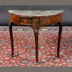 A George I walnut demi-lune table In need of restoration