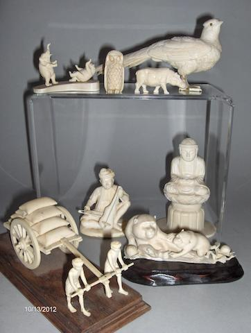 A group of eight carved ivory figures,to include a seated Buddha, a pheasant, a seated musician, figures pushing a cart on wood base and assorted miniature animals, including monkeys, hippo, owl etc,the pheasant 20cm long.