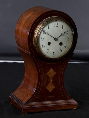 An Edwardian mahogany and inlaid balloon-shaped mantel clock