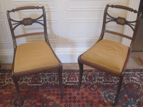 A set of three Regency rosewood brass strung dining chairs,with rope twist top rials, cut brass centred tablet backs, drop in seats, on sabre legs.
