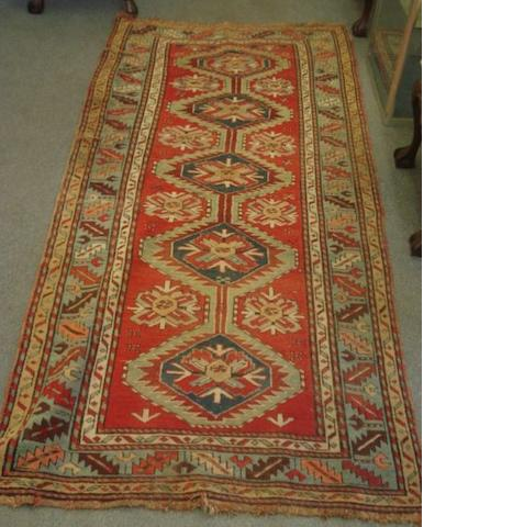 A Caucasian rug, with five lozenge pole medallions on a red ground, 2.65 x 1.15m and an Afgan rug. (2)