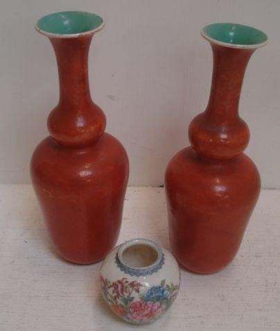 A small Chinese 'famille rose' baluster vase, bearing Yongzheng mark, 6.5cm, and a pair of orange glazed vases with trumpet shape necks, bearing Qianlong marks, 22.5cm. (3)