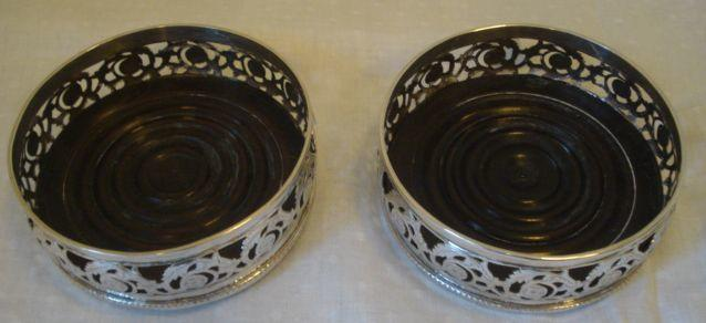A pair of Chinese silver bottle coasters, in the George III style, the sides with pierced scrolls and engraved with flower-heads, removeable wooden bases, 12cm diameter.