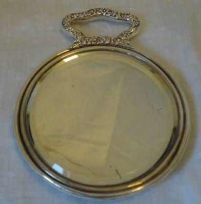 A pretty American silver backed hand mirror, of circular shape with shaped handle, stamped 'Sterling 925 fine',12.5cm.