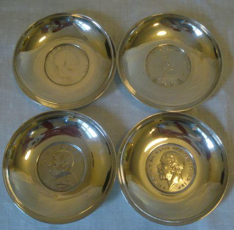 Four silver pin dishes, inset , two Chinese coins, 1935 Crown and George III Crown, all by A E Jones, Birmingham 1936.