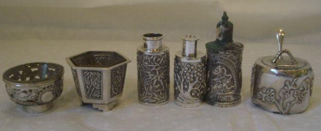 Six Chinese silver cruet items, by Wang Hing, to include a lidded mustard pot decorated with prunus, a salt cellar modelled as a planter on three shaped feet, a circular salt with dragon pierced sides, and three various pepperettes.