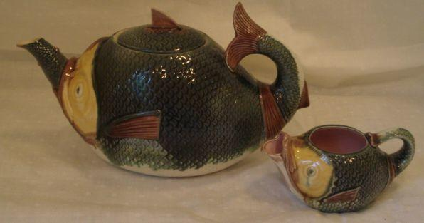 A 19th Century Majolica novelty teapot and matching milk jug, moulded as a fish, tails curling to form a handle, in an olive, ochre and brown glazes, length of teapot 26cm. (2)