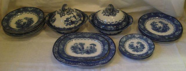 A Doulton part dinner service, blue transferred in the Watteau pattern comprising:- 2 pedestal dishes with domed covers, 5 plates, 26cm diameter, pair of oval serving dishes, one oval dish smaller, 6 bowls, 27cm diameter, and 5 plates, 19cm diameter.