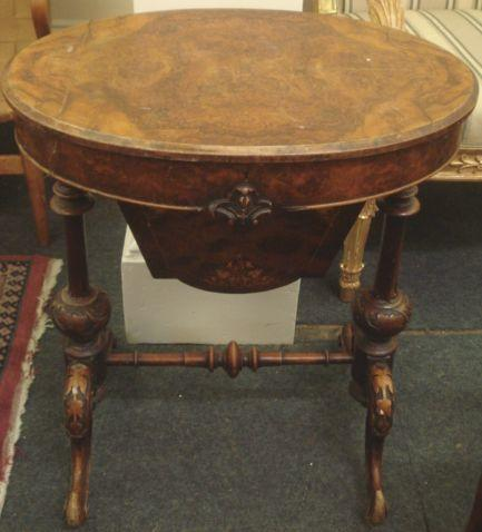 A Victorian figured walnut work table, oval shape, with lift top on carved turned supports, united by a pole stretcher, 62cm.