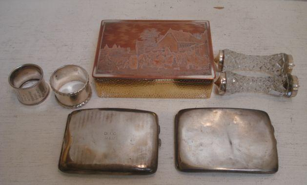 A pair of Edwardian mounted cut glass knife rests, Birmingham 1907, two silver cigarette cases, two silver napkin rings, one with decorated borders, Sheffield 1905, and an electroplate on copper cigarette box, the hinged cover decorated with a scene Kermesse Flamande after David Teniers, 10ozs weighable. (7)