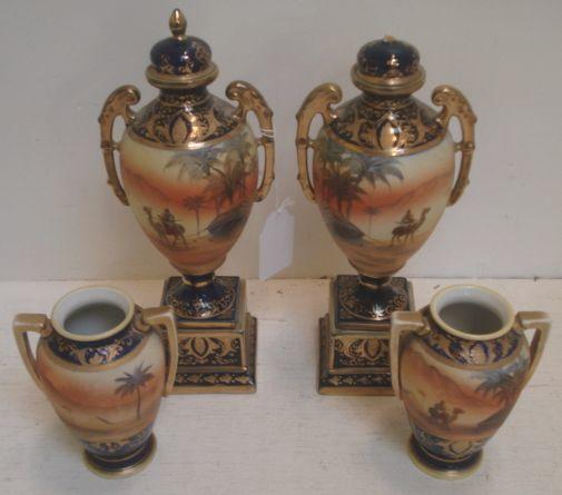 A garniture of four Noritake porcelain vases, painted around the sides with desert scenes, deep blue grounds heightened with gilding, the tallest 30cm.