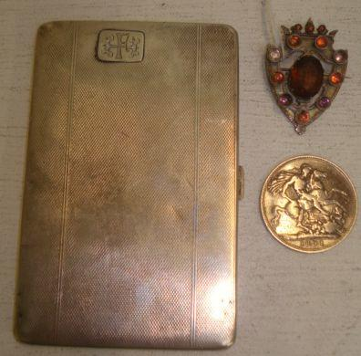 An engine turned silver cigarette case, Chester 1927, 6ozs, a Victorian Scottish multi-gem set shield shape brooch, altered, registration marks, and a Queen Victoria 1891 silver Crown. (3)