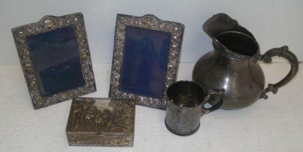 A pair of late Victorian / Edwardian silver mounted easel photograph frames, H Matthews, marks unclear, foliate embossed, a Britannia metal baluster shape water jug, foliate decorated, Buenos Aires retailer, Reed & Barton christening can and a Japanese silvered metal cigarette box. (5)