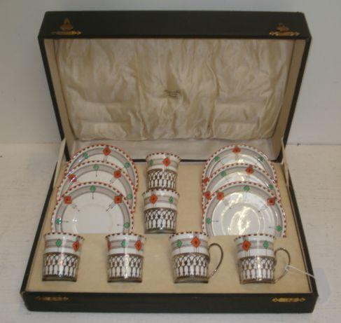 A cased Art Deco silver and porcelain coffee service, Six cups and saucers, the Shelley geometric pattern porcelain in Gothic style pierced silver cage mounts with scroll handles, Adie Brothers, Birmingham 1932.