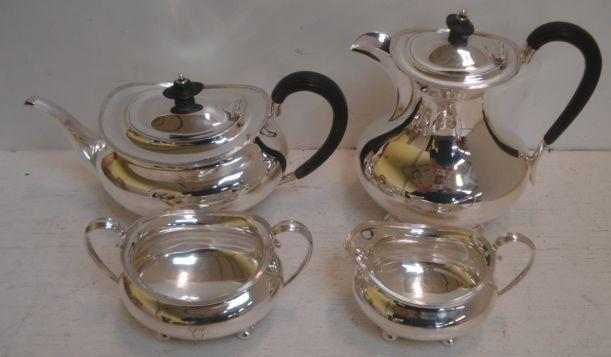 A Regency style four piece silver tea service, Harry Wright Atkin, Sheffield 1921-1923, of oval form with threaded edges, on bun feet, the tea and hot water pots with blackwood scroll handles and finials, 54ozs, initialled 'C'.