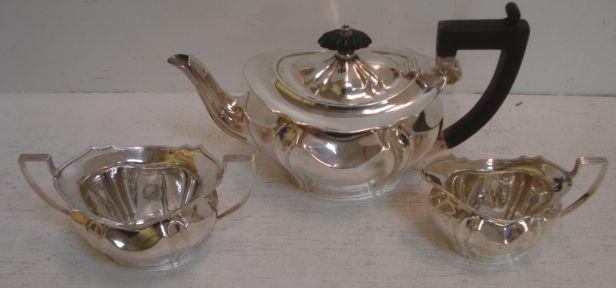 A late Victorian silver three piece bachelor tea service, makers mark C.E.N., Sheffield 1898, of shaped oval form, the teapot with blackwood handle and finial, 15ozs.