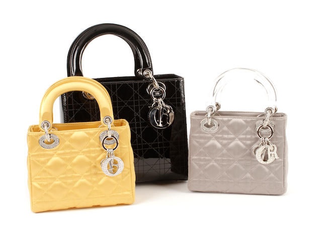 Three Lady Dior bags - one in patent black leather, one in golden satin and the other in silver coloured satin