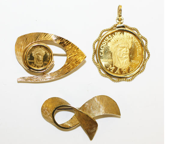 Two Venezuelan commemorative coins mounted as a pendant and brooch and a further brooch,