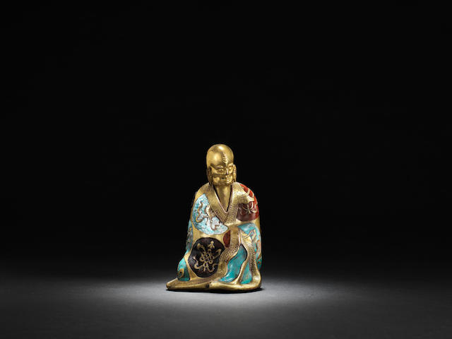 A gilt-bronze and champleve enamelled figure of a luohan Mid Qing dynasty