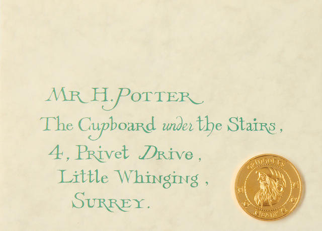 Harry Potter: A collection of memorabilia including - a gallion coin, a Gringotts banks paying in slip and a 'Cupboard Under The Stairs' letter