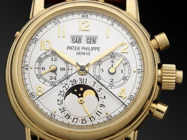Patek Philippe. A very fine and rare 18ct gold manual wind perpetual calendar split seconds chronograph wristwatch with moon phases Certificate of Origin and fitted Patek Philippe boxRef:5004, Case No.2984901, Movement No.879513, Circa 1998