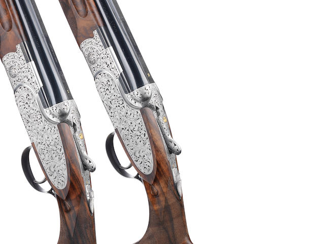 A fine pair of G. Arici-engraved 12-bore (3in) 'SO1O' single-trigger over-and-under sidelock ejector guns by P. Beretta, no. SOG061B/2B In their leather case together with makers certificates, manuals and accessories