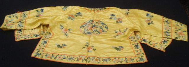 A Chinese yellow silk jacket, embroidered with flowers and fabulous creatures.