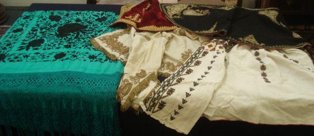 A turquoise silk shawl, embroidered in black with trailing flowers, having a deep turquoise fringe, a black cape with golden wire embroidery, a child's embroidered red velvet jerkin, an embroidered jacket and an ivory coloured jacket with golden wire embroidery. (5)