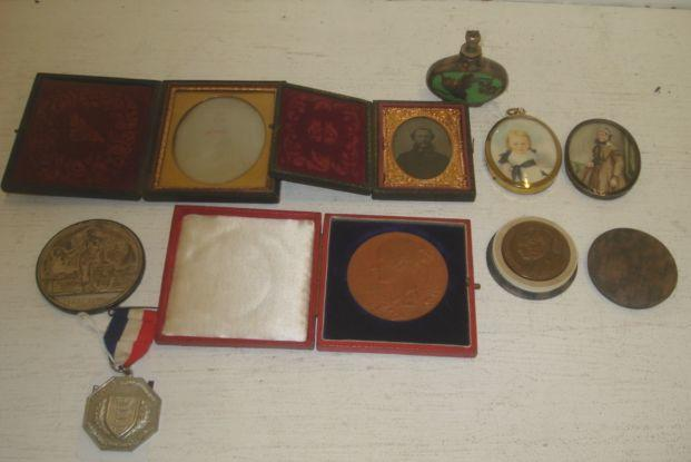 A collection of Queen Victoria and George V Commemorative medals, Victorian daguerreotype photographs in fitted cases, a Victorian portrait miniature of a lady, standing three quarter length beside a chair, watercolour on ivory, another of an infant and an Art Nouveau metalware overlaid green porcelain perfume bottle with crown stopper.