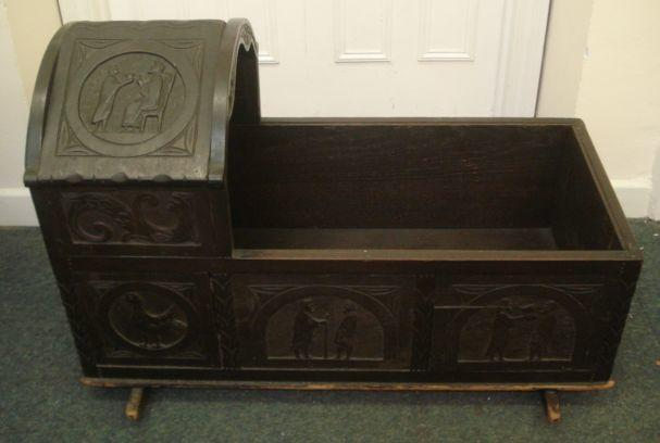 A mid 18th Century oak cradle, with arched hood, carved with a date '1754' and panels of figures, chickens and leaf scrolls, on rockers, 97cm.
