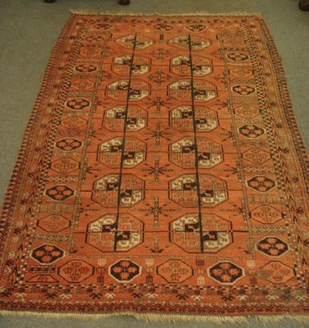 An Afgan rug, with two rows of quartered guls, on a rust ground, 2.1 x 1.3m.