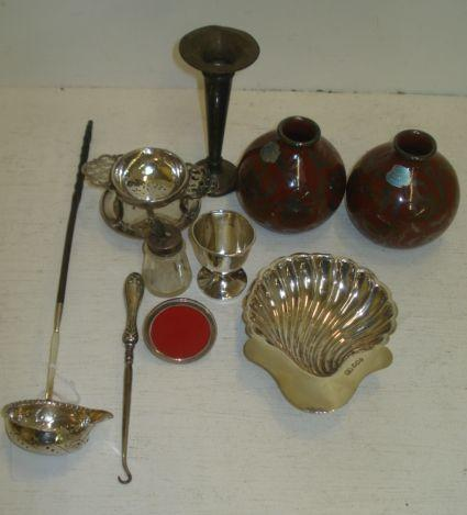 An Edwardian silver shell butter dish, Lee & Wigful, Sheffield 1903, on ball feet, and the following silver, a Georgian punch ladle, with twist whalebone handle, side pouring, tea strainer and drip stand, The Alexander Clarke Company, Birmingham 1925, an egg cup, trumpet spill vase, mounted glass glue pot, button hook also a small metalware photograph frame and a pair of Arento Firenze vases.