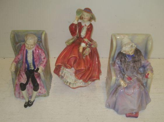 A pair of Royal Doulton figures, 'Darby & Joan', HN2023 and 2024, each seated in a chair and another 'Top o' The Hill', HN 1834. (3)