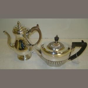 A George III style silver baluster shape coffee pot, makers mark C.E., 1933, with domed hinged cover, wooden scroll handle and a George III style oval teapot, Goldsmiths & Silversmiths Company, Sheffield 1911, embossed with lobes and fluted, blackwood handle and finial, 33ozs. (2)