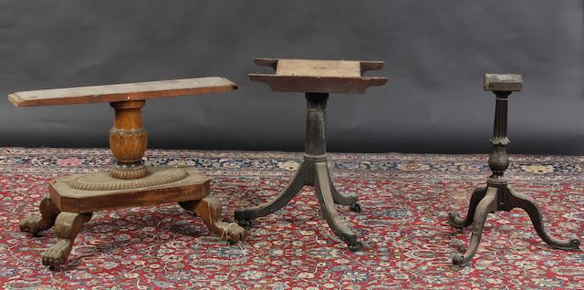 A Chippendale style carved mahogany tripod base with acanthus carving, together with a George III mahogany dining table pedestal, and a William IV style breakfast table base with paw feet. (3)