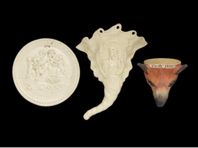 A creamware wall pocket, a plaque and a fox head stirrup cup, circa 1775-1800
