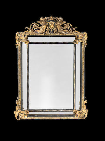 A French early 20th century parcel-gilt and ebonised mirror