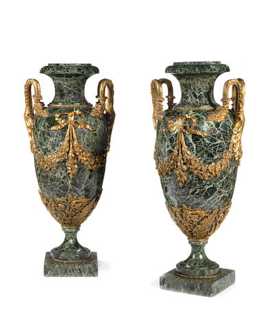 A large pair of green marle urns with entwined snakes