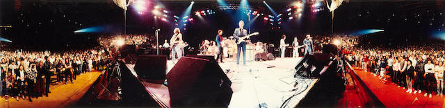 A panoramic colour photograph of Eric Clapton, Jimmy Page and Jeff Beck onstage, The Forum, Los Angeles, December 5th/6th, 1983, Ronnie Lane's 'ARMS' (Action into Research for Multiple Sclerosis) benefit concert,