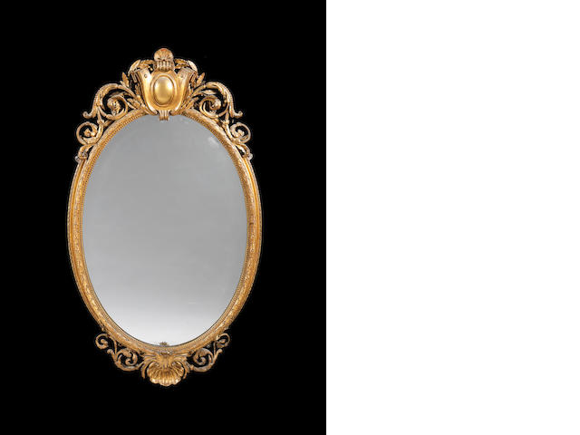 A French late 19th century giltwood oval over-mantel mirror