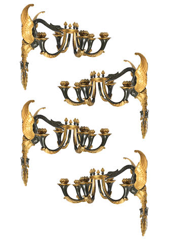 A set of four early 20th century Empire style patinated and parcel-gilt appliques