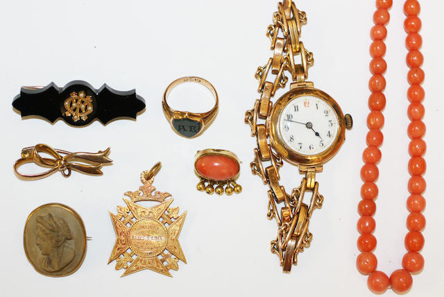 A collection of jewellery in a small brown case,