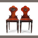 A pair of late Regency mahogany hall chairs