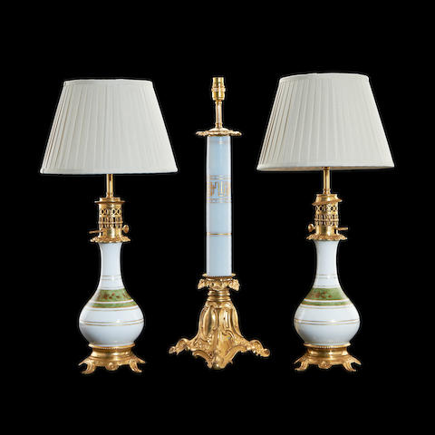 A pair of gilt metal and coloured glass moderator lamps together with a larger similar lampin the Chinese taste