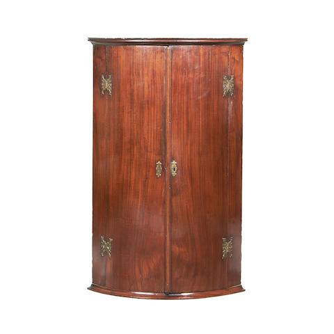 A George III mahogany hanging bowfront corner cupboard