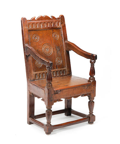 A 17th century oak wainscote chair, later seat and base back legs