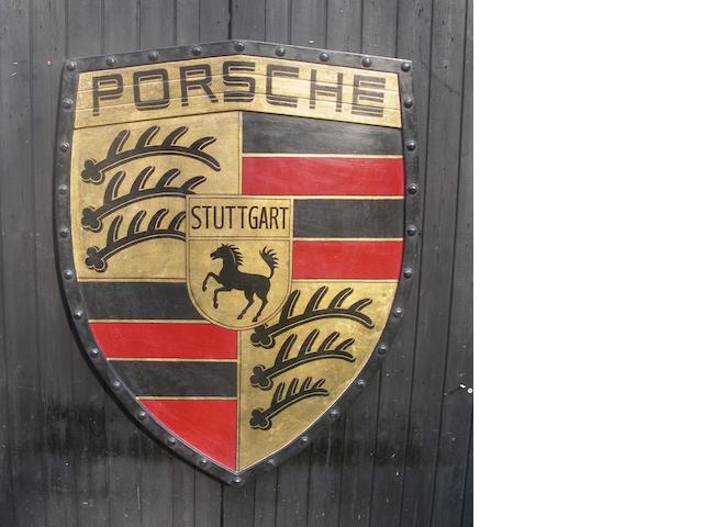 A hand-painted 'Porsche' garage display emblem,