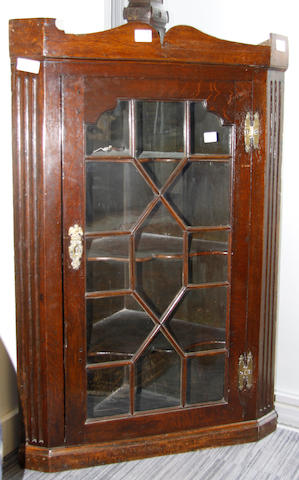 A late George III oak corner cupboard,