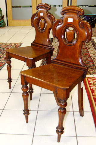 A pair of mid-Victorian mahogany hall chairs,
