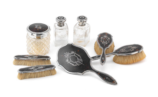 A matched  silver and tortoiseshell   toilet set by Charles Henry Dumenil, the bottles by Goldsmiths & Silversmiths Co Ltd, London 1916-18  (7)